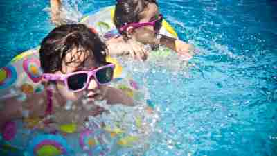 Two girls with ADHD swimming in pool with sunglasses as part of structured day