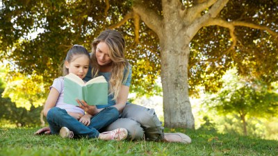 Mother and daughter building academic skills by reading book under tree in the summer