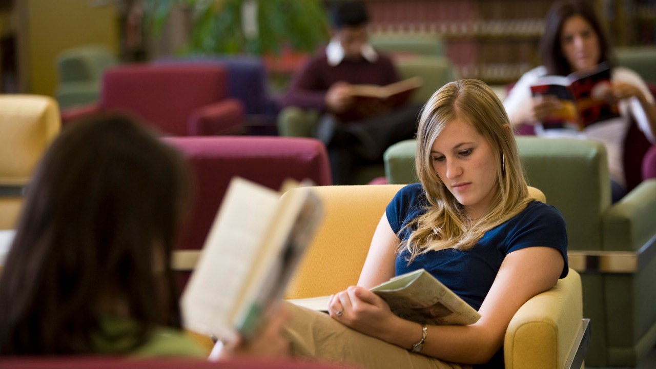Student with ADHD reading in library preparing to apply for scholarships