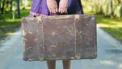 A young adult with ADHD holds a suitcase because she's moving back home