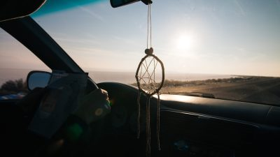 Independence Teen driving with Dreamcatcher haning on rear view mirror