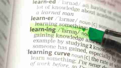 "Close up of word ""learning"" highlighted in dictionary belonging to ADHD person"