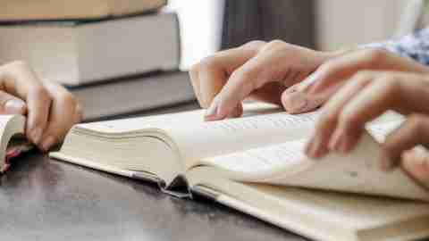 Hands of person with ADHD flip through textbook at table