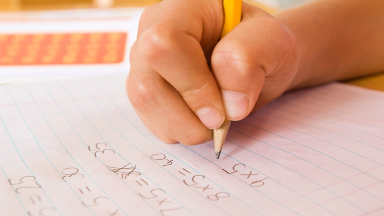 A child's hand completing a homework assignment with the help of math accommodations