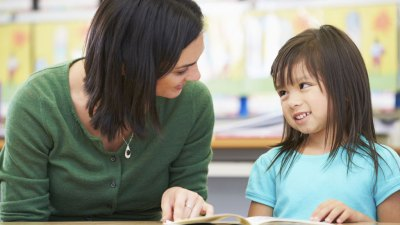 Teacher assisting little girl with ADHD at school