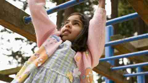 Girl with ADHD playing on monkey bars are focusing during recess
