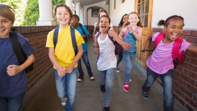Group of schools kids with ADHD running down hallway to class.