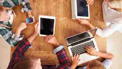 High-teach family of four with ADHD on laptop, cell phone, and ipad