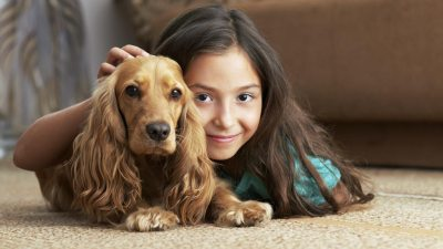 Girl with ADHD in living room with pet dog