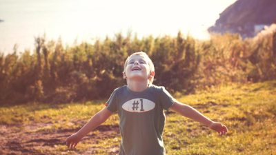 A boy with ADHD throws his arms open and practices deep breathing exercises outside to manage anxiety.