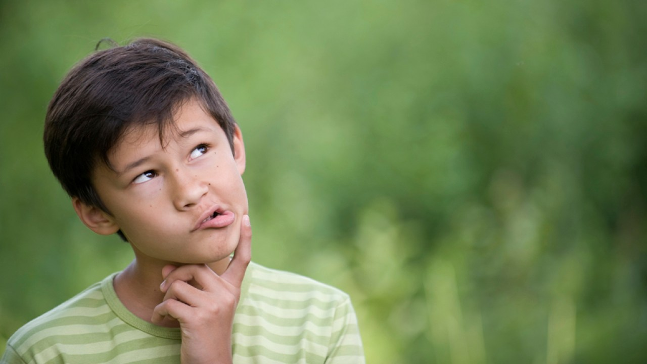 Confused boy with Auditory Processing Disorder walking outside with finger on chin