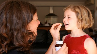 Mother placing fish oil pill in ADHD daughter's mouth in kitchen