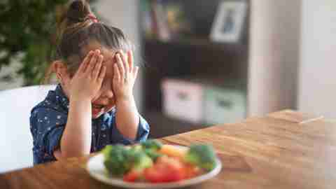 Girl with ADHD covers face with hand while sitting in front of plate of vegetables