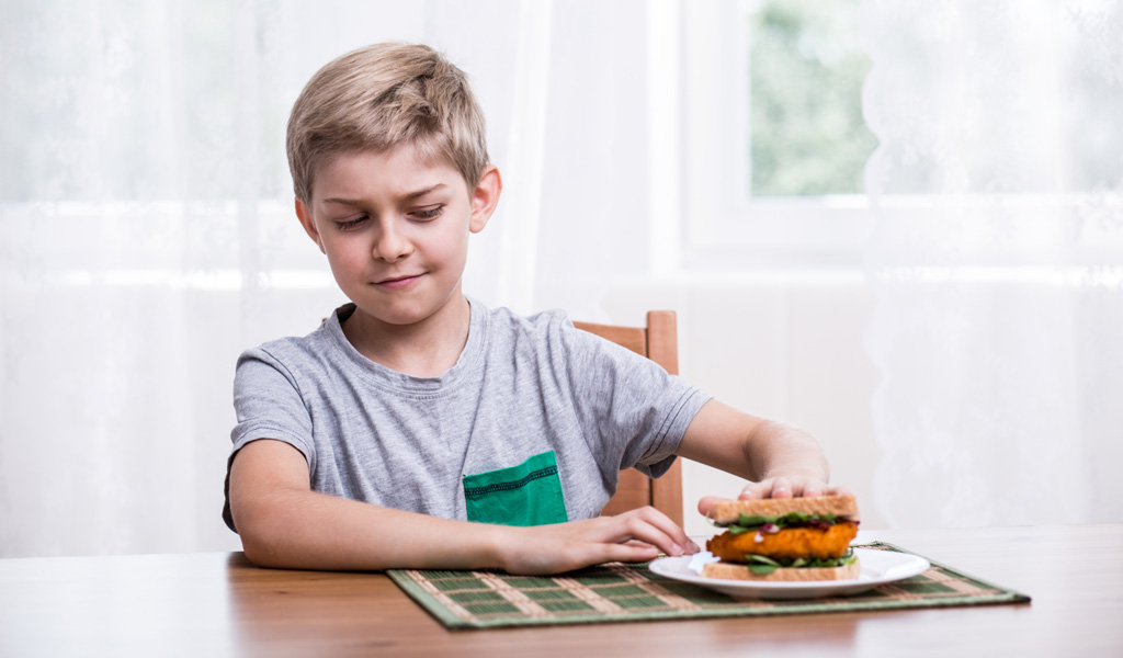 Boy with ADHD pushes away chicken sandwich at table after losing apetite from treatment