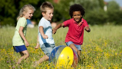 Three children with ADHD playing with beach ball in field outside, well-behaved thanks to a new ADHD medication