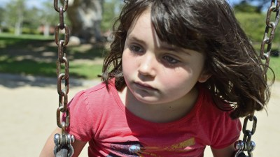Sad girl with Sensory Processing Disorder and ADHD on swing at park