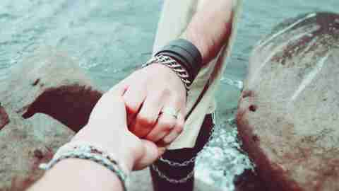 Two people with ADHD holding hands by ocean and supporting eachother