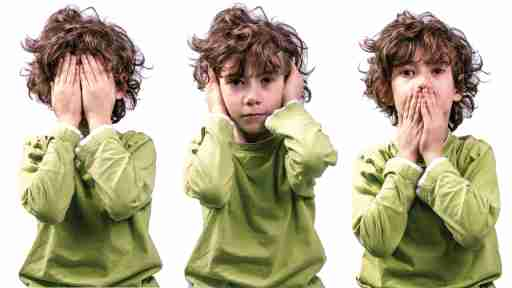 A boy with autism and ADHD covers his face with his hands.