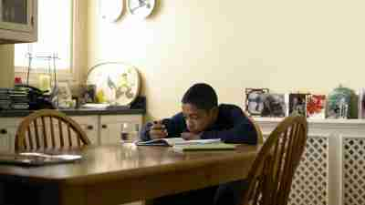 A boy sits at the kitchen table and makes excuses for not doing homework