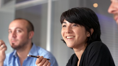 A woman with ADHD smiles in a meeting at work