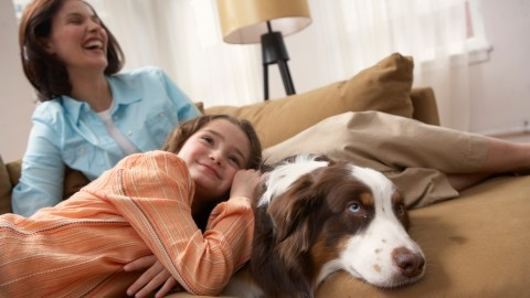 Mother with daughter with ADHD (8-10) relaxing on sofa with dog, smiling
