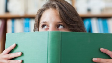 Female student holding a book about how ADHD is real.
