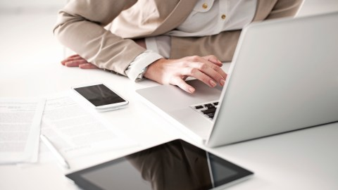 A woman uses productivity apps on he phone and tablet to help her stay on task at work.