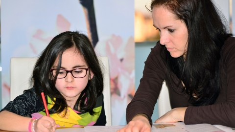 A mom helps her child with homework, giving her the tools she needs to succeed.