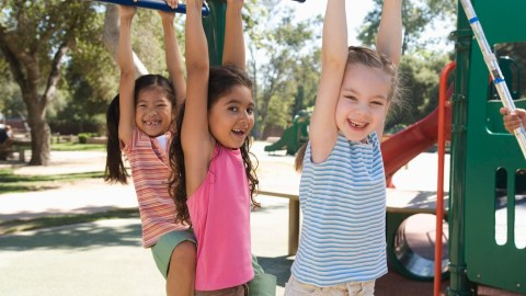 Girls playing on monkey bars, a common exercise idea for kids