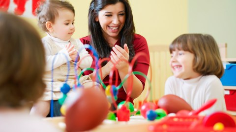 A therapist works with two children to help them manage hypersensitivity.