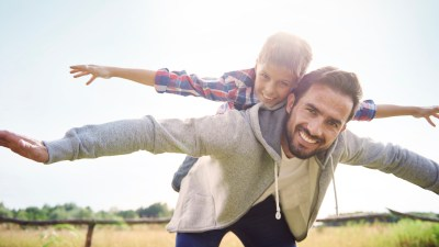 A father and son play airplane together. Their seal for life is an ADHD superpower.