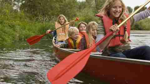 Family enjoying a nice canoe trip after following these travel tips