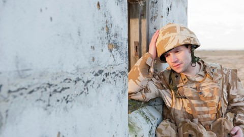 A soldier with PTSD, a form of anxiety disorder, leans against a building.