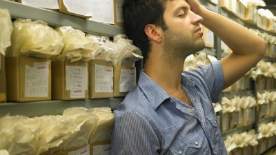 A man with anxiety leans against the wall in a storage area with his eyes closed.