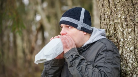 A man breathes into a paper bag to help stop a panic attack.