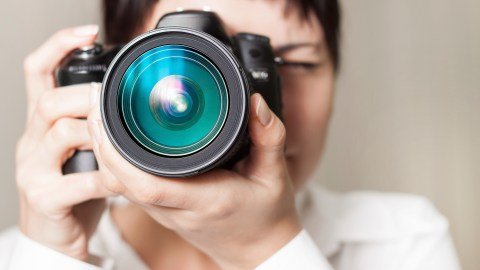 A woman with ADHD looks through a zoom lens camera.