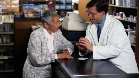 A pharmacist explaining to an older woman how she should treat her mood disorder