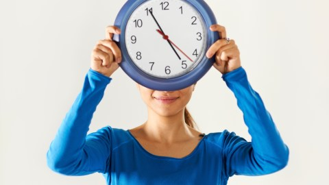 A woman with a mood disorder, holding a blue clock in front of her face