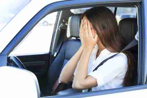 A woman covers her face with her hands in the car and wonders how to stop her anxiety
