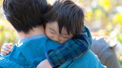 A boy with ADHD hugs his father after a hard day