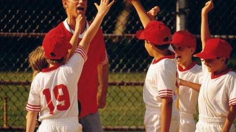 A baseball coach and his players with ADHD cheer after winning a game