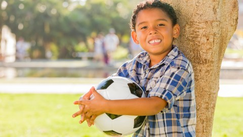 A boy with ADHD holds a soccer ball and leans against a tree in a park