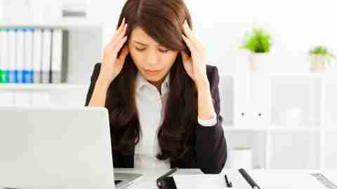 A businesswoman experiencing ADHD stress puts her head in her hands at her office desk