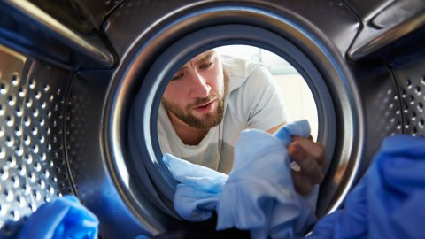 A man looking into a dryer is experiencing ADHD stress because he dyed his clothes blue