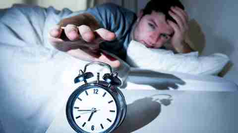 A man with ADHD turns off his alarm clock