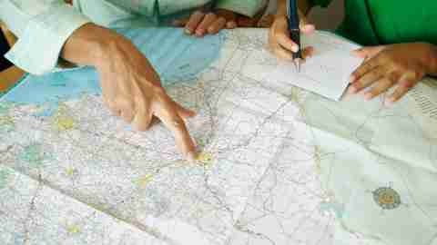 A woman with ADHD plans a route on a map, a metaphor for planning how to stop wasting time