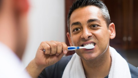 A man with ADHD brushes his teeth as part of his time-saving morning routine