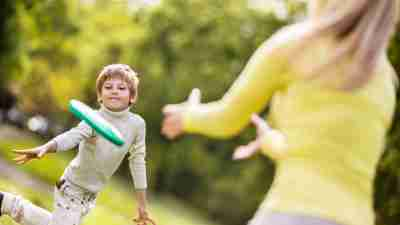 A mother plays frisbee with her son with ADHD and SPD