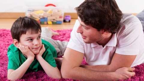 Young boy lying on the floor talking about the side effects of his ADHD medication with his dad