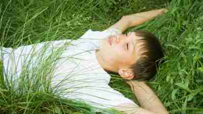 Boy laying on the grass as he ponders the side effects of his ADHD medication
